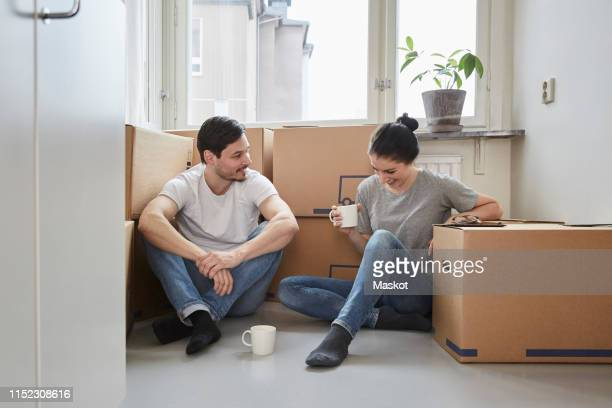 smiling couple talking while enjoying coffee during moving house - financiën en economie stockfoto's en -beelden