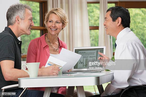 Smiling couple talking with financial advisor at table