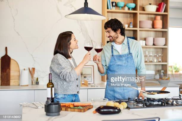 smiling couple toasting wineglasses in kitchen - mid adult women stock pictures, royalty-free photos & images