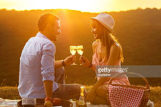 Smiling couple toasting with wine on picnic at sunset.