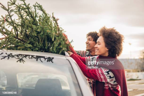 smiling couple tying christmas tree to a car - car decoration stock pictures, royalty-free photos & images