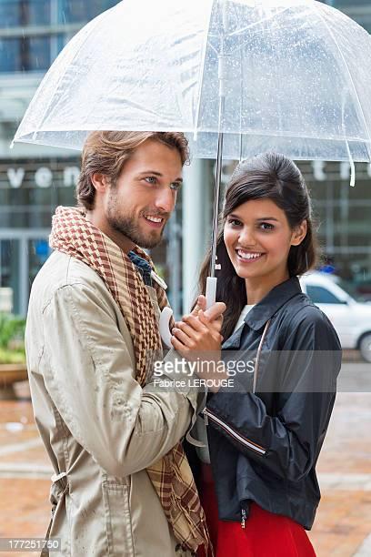 Smiling couple under an umbrella