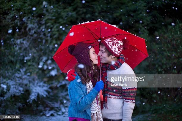 Smiling couple under umbrella in snow