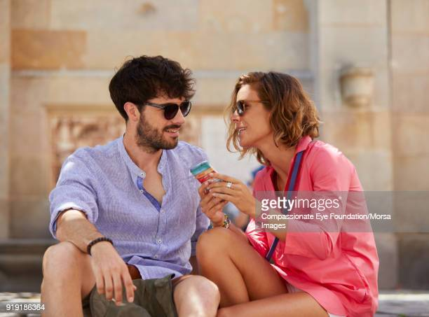 Smiling couple using cell phone on street in Barcelona