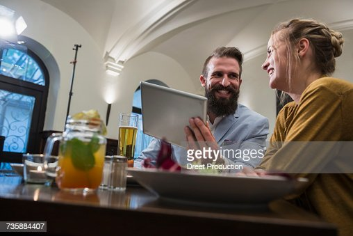 Smiling couple using digital tablet at restaurant
