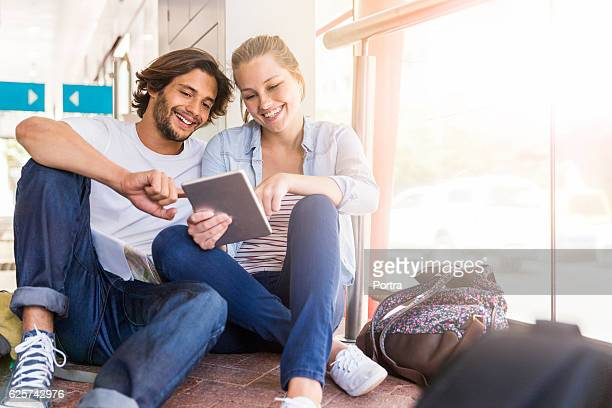Smiling couple using digital tablet at station