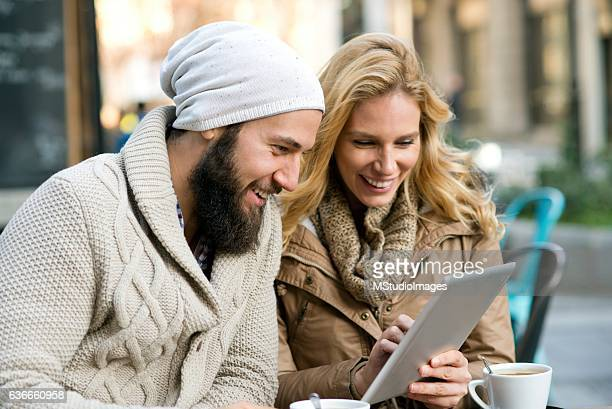Smiling couple using digital tablet.