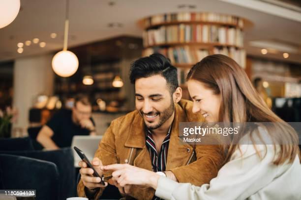 smiling couple using smart phone while sitting in restaurant - relationship stockfoto's en -beelden