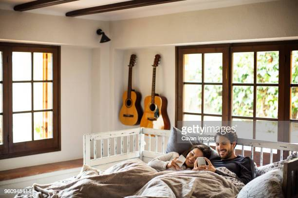 Smiling couple using smart phones while lying on bed at home