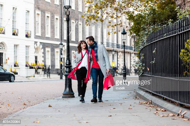 Smiling couple walking along the street with shopping bags