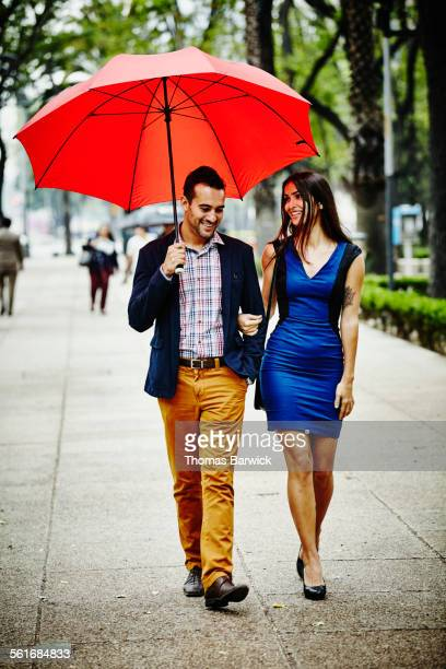 Smiling couple walking arm in arm under umbrella