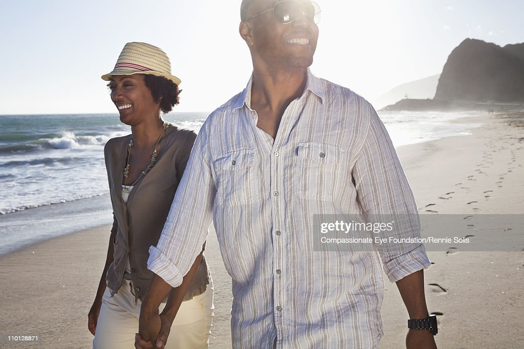 Smiling couple walking hand in hand down the beach : Stock Photo