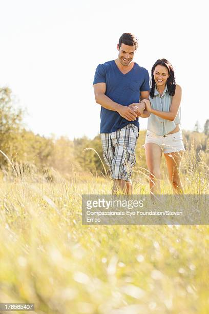 smiling couple walking in long grass - cef do not delete stock pictures, royalty-free photos & images
