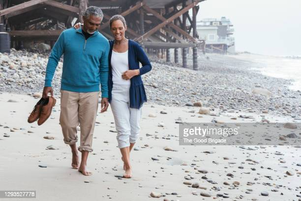 smiling couple walking on beach - married stock pictures, royalty-free photos & images