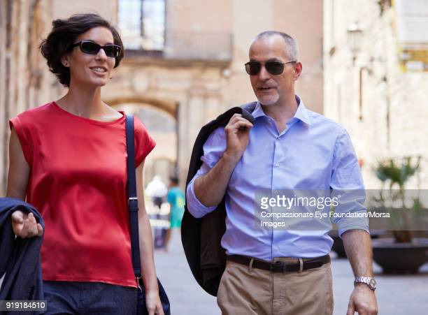 smiling couple walking on street in barcelona - sleeve stock photos and pictures