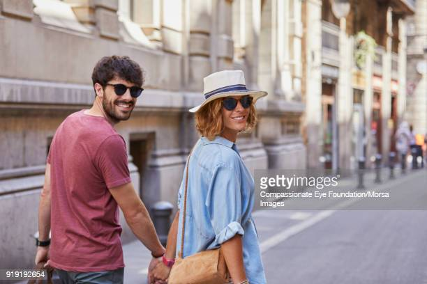 Smiling couple walking on street in Barcelona