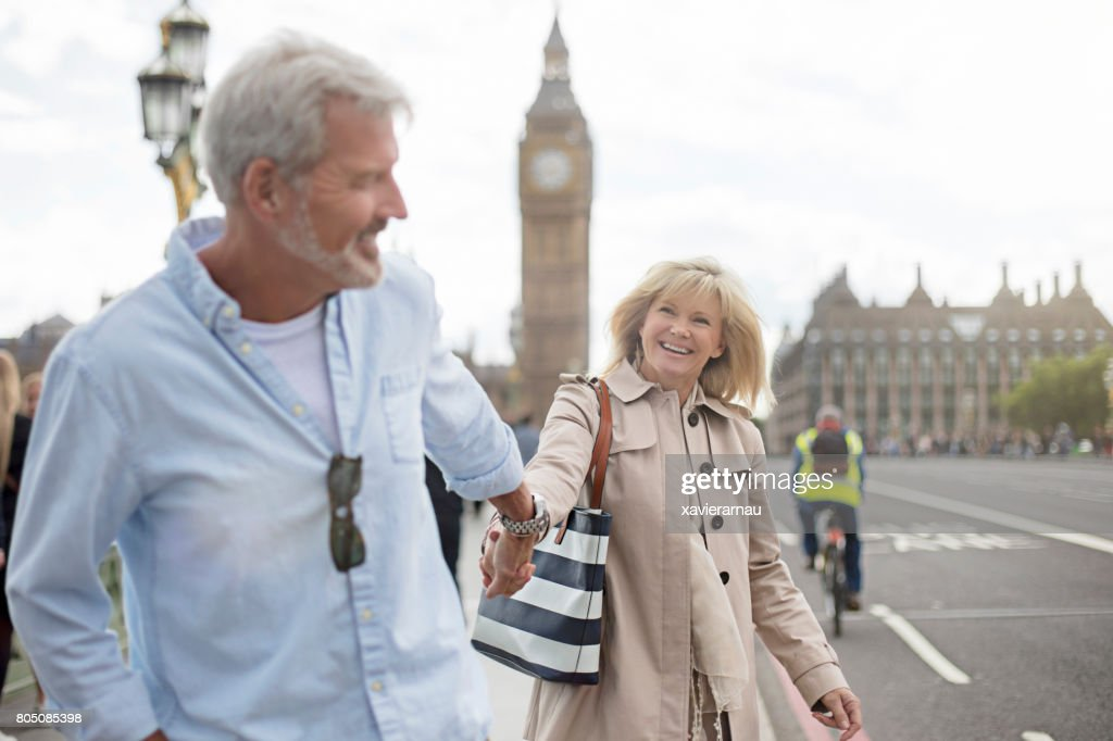 Smiling couple walking on Westminster Bridge : Stock Photo