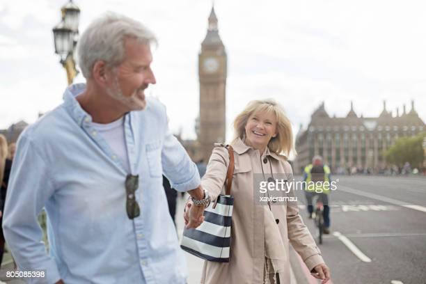 Smiling couple walking on Westminster Bridge