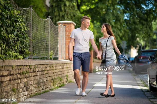 Smiling couple walking together on sidewalk