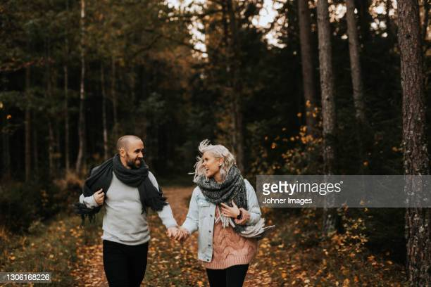 smiling couple walking together - västra götaland county stock pictures, royalty-free photos & images