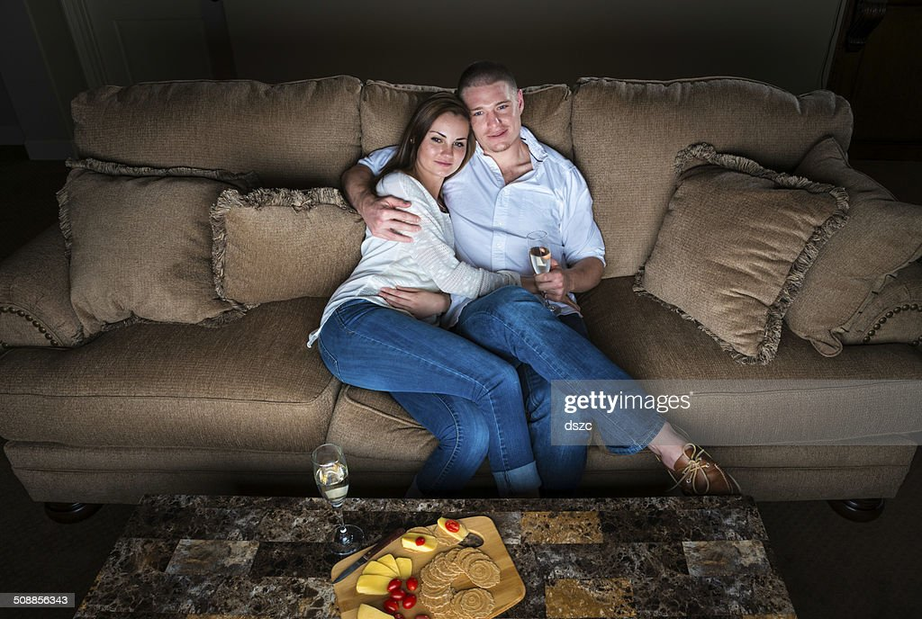 Smiling couple watches TV romance sitting on sofa with wine : Stock Photo