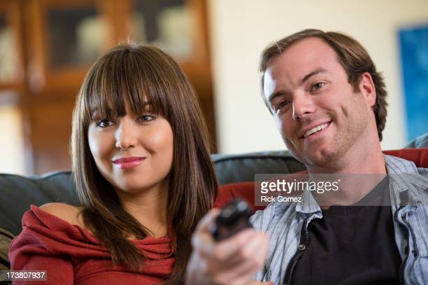 smiling couple watching television on sofa - changing channels stock photos and pictures
