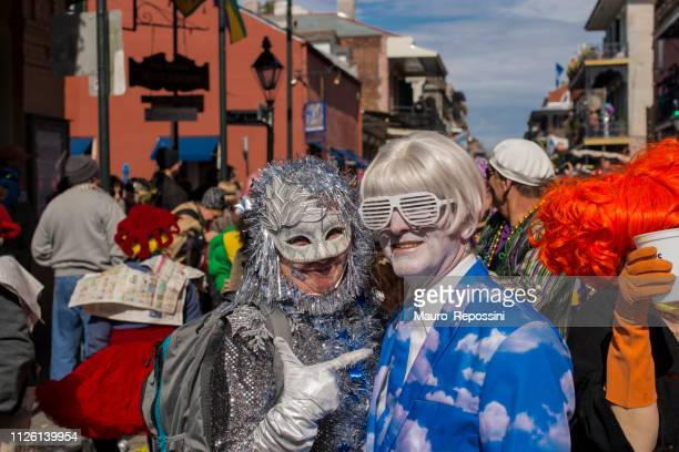 a smiling couple wearing costumes in the street during the mardi gras celebration at new orleans carnival, louisiana, usa . - creole ethnicity stock pictures, royalty-free photos & images