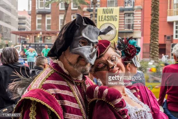 a smiling couple wearing costumes in the street during the mardi gras celebration at new orleans carnival, louisiana, usa . - mardi gras fun in new orleans stock photos and pictures