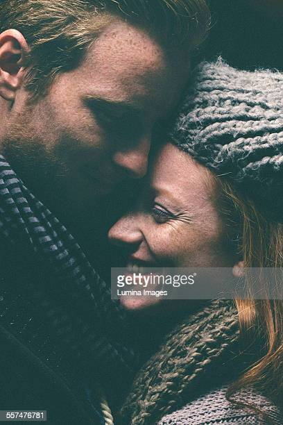 Smiling couple wearing warm clothing hugging
