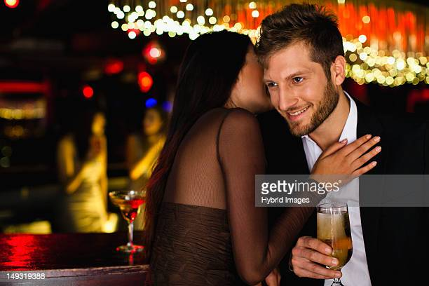 Smiling couple whispering at bar