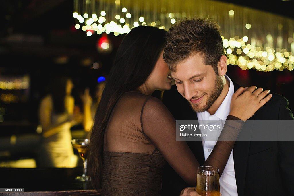 Smiling couple whispering at bar : Stock Photo