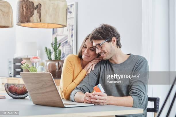 smiling couple with a card using laptop on table at home - vestido de renda - fotografias e filmes do acervo
