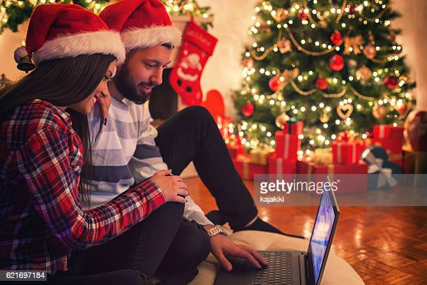 Smiling Couple With a Laptop on Christmas Eve