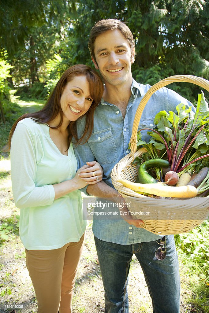 Smiling couple with basket of vegetables : Stock Photo