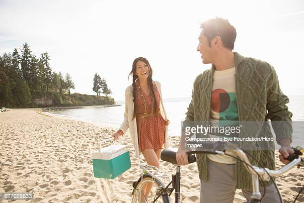 Smiling couple with bicycle on beach