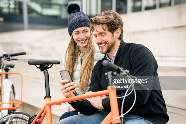 smiling couple with bicycles and cell phone in the city - mobilität stock-fotos und bilder