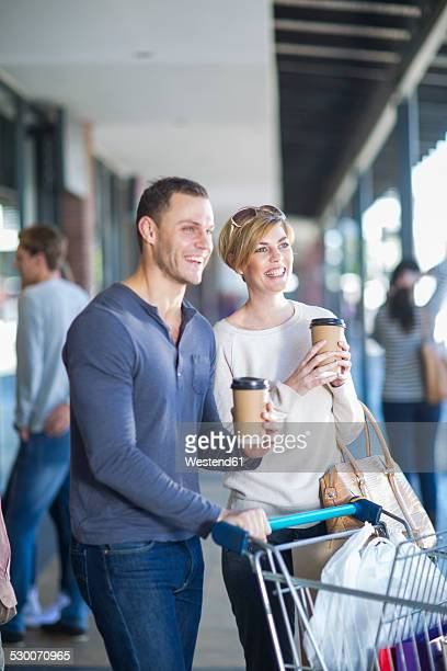 Smiling couple with coffees to go on shopping tour