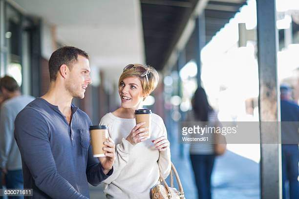 Smiling couple with coffees to go