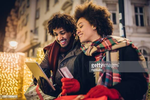 Smiling couple with credit card and digital tablet