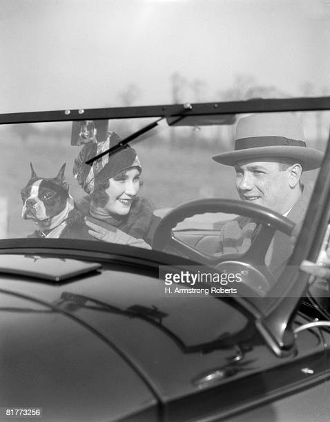 Smiling Couple With Dog Boston Terrier In Front Seat Of Convertible View Through The Windshield Into The Car Man At Steering Wheel Fashion Hats.