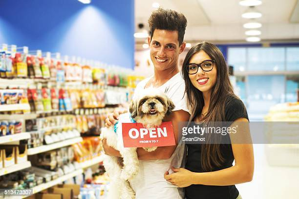 Souriant Couple avec chien dans un magasin pour animaux de compagnie