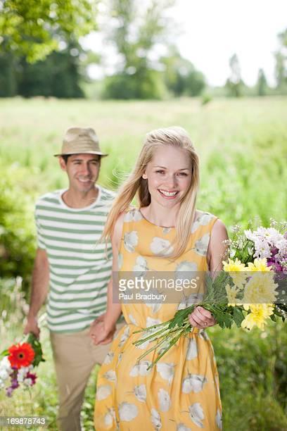couple souriant avec fleurs dans la campagne du terrain