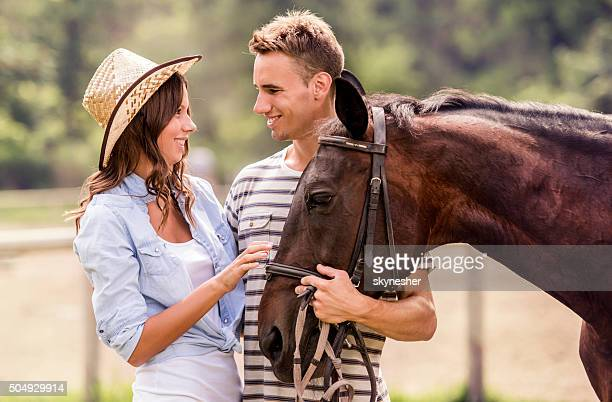 Smiling couple with horse talking to each other.