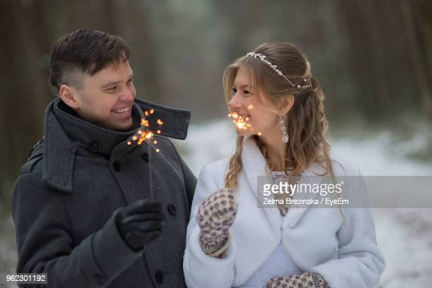 Smiling Couple With Sparklers Looking Face To Face During Winter