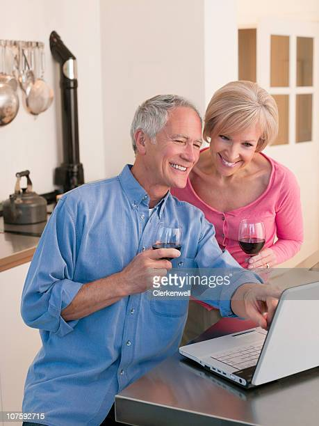 Smiling couple with wine glasses pointing at laptop