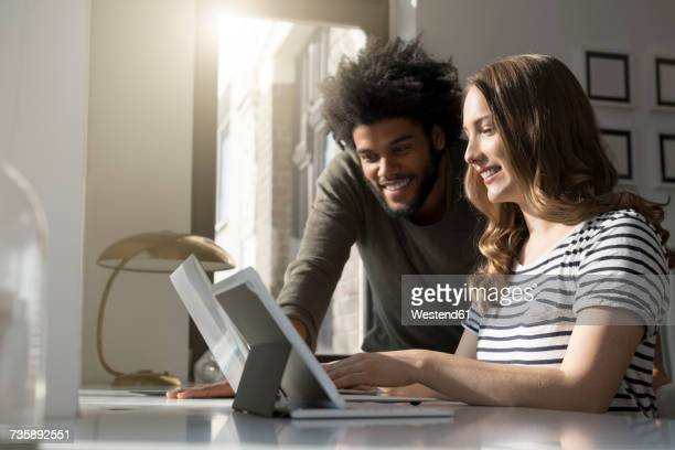 smiling couple working at home with laptop and tablet - etnia imagens e fotografias de stock