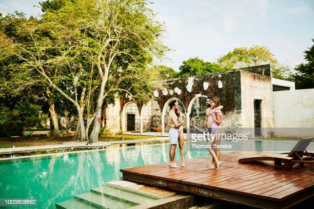 Smiling couples hanging out together at edge of pool at luxury tropical resort