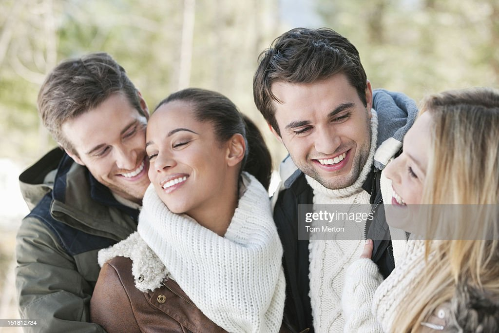 Smiling couples hugging : Stock Photo