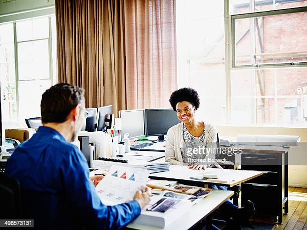 Smiling coworkers in discussion at desk in office