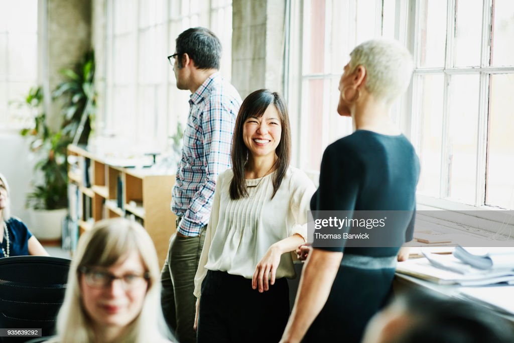 Smiling coworkers in discussion in design studio : Stock Photo